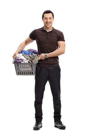 Full length portrait of a happy guy with a laundry basket full of clothes isolated on white background