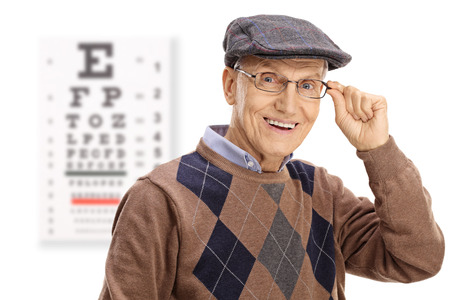Elderly man smiling in front of an eye chart isolated on white background
