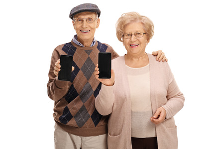 Cheerful seniors showing phones to the camera isolated on white background Foto de archivo