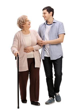 Full length portrait of a young man helping a mature woman with a walking cane isolated on white background Stock Photo