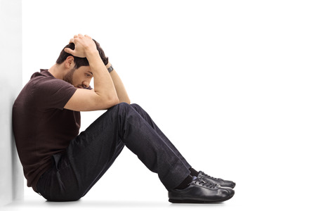 Deprimido hombre sentado en el suelo con la cabeza hacia abajo y apoyado en una pared aislada sobre fondo blanco