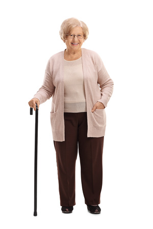Full length portrait of an elderly woman with a walking cane smiling isolated on white background