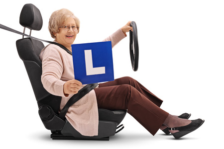 Elderly woman sitting in a car seat and showing an L-sign isolated on white background