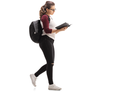 Full length profile shot of a female student with a backpack walking and reading a book isolated on white background Foto de archivo