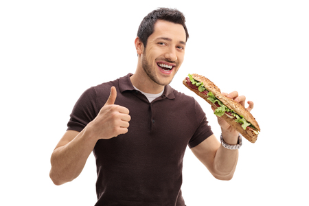 Young man having a sandwich and making a thumb up gesture isolated on white background Banque d'images