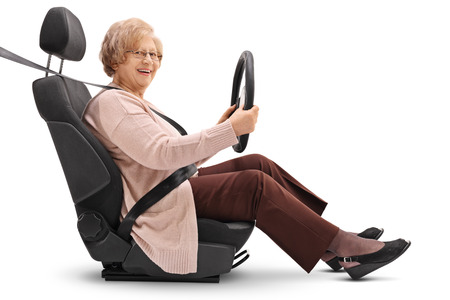 fastened: Elderly woman seated in a car seat holding a steering wheel and looking at the camera isolated on white background