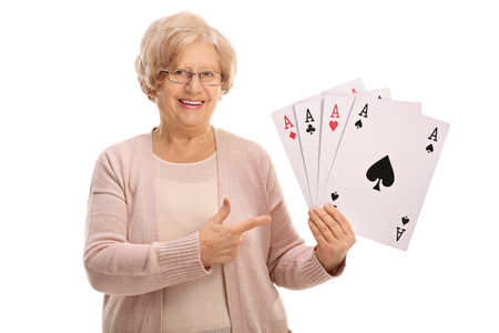 Mature woman holding four aces and pointing isolated on white background