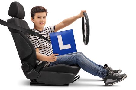 Zitting van de jongen in een auto zitten en het tonen van een L-teken op een witte achtergrond Stockfoto
