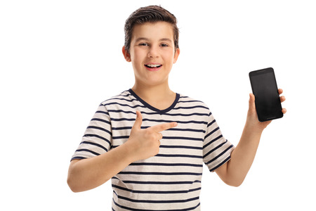 showing: Joyful boy holding a phone and pointing isolated on white background Stock Photo