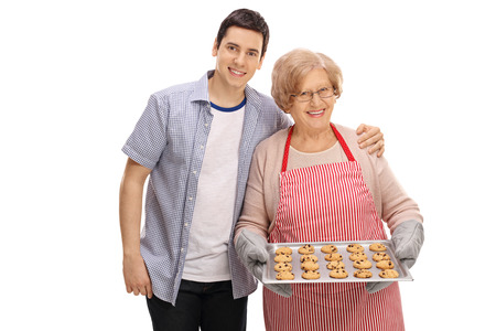 Young man and an old lady with a tray of freshly baked cookies isolated on white background Stock Photo