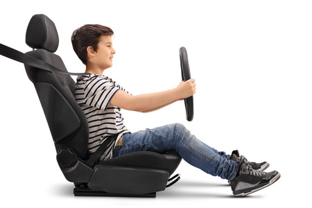 Boy sitting on a car seat and holding a steering wheel pretending to drive isolated on white background
