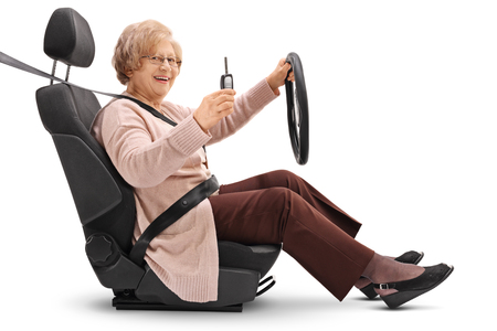 fastened: Joyful elderly woman holding a car key and sitting in a car seat isolated on white background