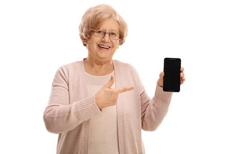 Oudere dame die een telefoon en wijzend op een witte achtergrond Stockfoto