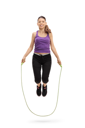saltar: Full length portrait of a female athlete exercising with a skipping rope isolated on white background Foto de archivo