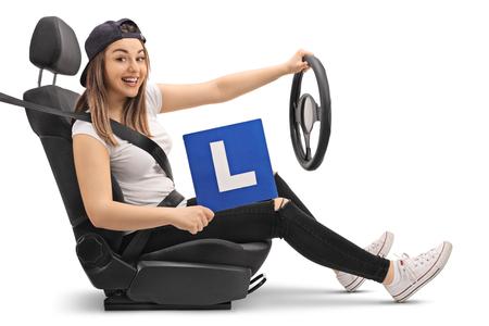 La ragazza felice in possesso di un L-sign e fingendo di guidare in un seggiolino per auto isolato su sfondo bianco