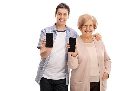 Giovane uomo e una donna matura che mostra i telefoni alla fotocamera isolato su sfondo bianco Archivio Fotografico