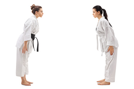 Full length profile shot of two young women dressed in kimonos bowing to each other isolated on white background