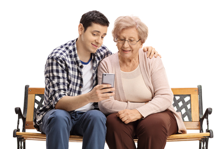 cellphones: Young man sitting on a bench with a mature woman and showing her something on a phone isolated on white background