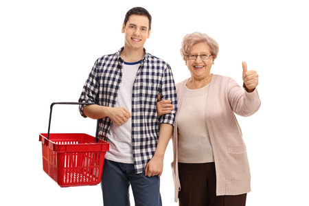 Cheerful guy with an empty shopping basket and a mature lady giving a thumb up isolated on white background Stock Photo