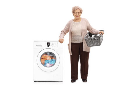 Full length portrait of an elderly woman with an empty laundry basket standing next to a washing machine isolated on white background