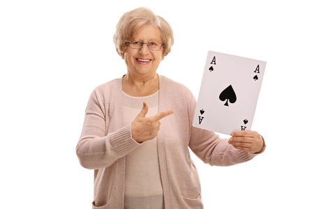 Joyful mature lady holding an ace of spades card and pointing isolated on white background
