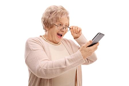 Opgewekte oudste die een telefoon bekijkt die op witte achtergrond wordt geïsoleerd