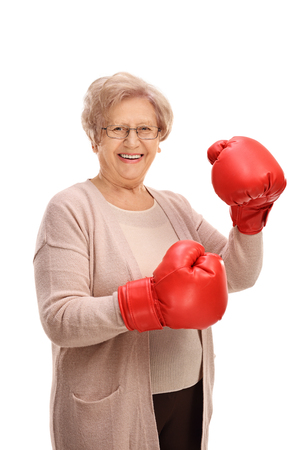 Happy elderly woman wearing a pair of boxing gloves isolated on white background