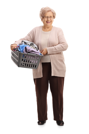 Full length portrait of a mature woman holding a laundry basket filled with clothes isolated on white background Stock Photo