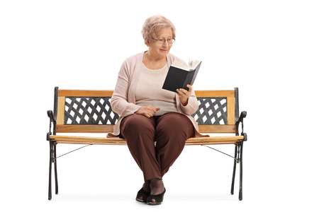 Senior sitting on a bench and reading a book isolated on white background Stock Photo