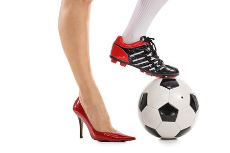Kobieta z jedną nogą w butach na wysokim obcasie, a inne w butach piłkarskich naciskając piłkę nożną na białym tle