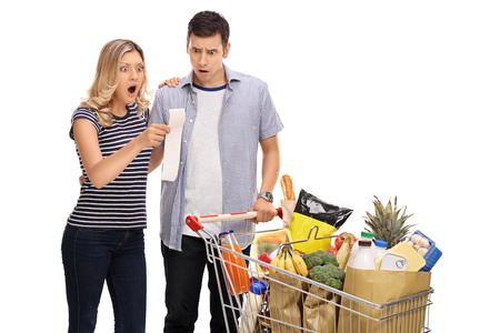 Choqué jeune couple regardant un projet de loi d'achats isolé sur fond blanc Banque d'images