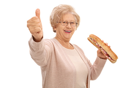 Happy elderly woman with a sandwich making a thumb up sign isolated on white background