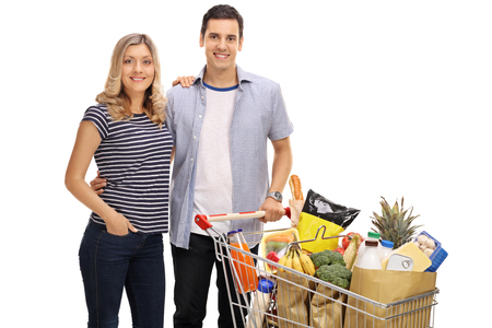 Happy young couple with a shopping cart full of groceries isolated on white background