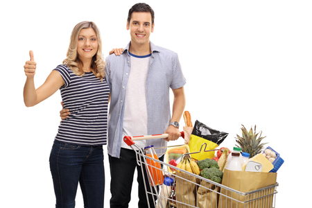 pareja abrazada: Mujer joven que da un pulgar hacia arriba y un hombre joven con una cesta llena de comestibles aisladas sobre fondo blanco