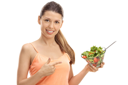 Happy girl holding a salad and pointing isolated on white background