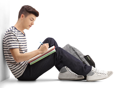 Teen student writing in a notebook and leaning against a wall isolated on white background
