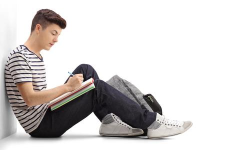 Tudiant étudiant dans un cahier et appuyé contre un mur isolé sur fond blanc Banque d'images - 73814765