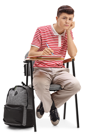 Bored teenage student sitting in a chair and looking at the camera isolated on white background Stock Photo