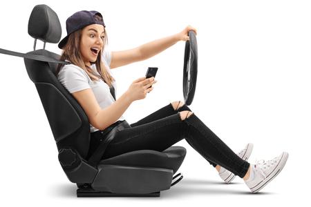 Adolescente que conduce y que mira su teléfono aislado en el fondo blanco
