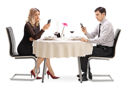 ignore: Young man and woman sitting at a restaurant table and looking at their phones isolated on white background