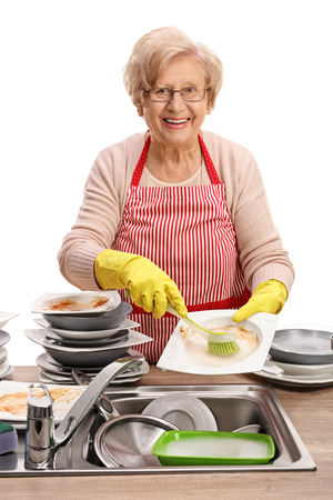 Mature woman cleaning the dishes with a brush and looking at the camera isolated on white background Stock Photo