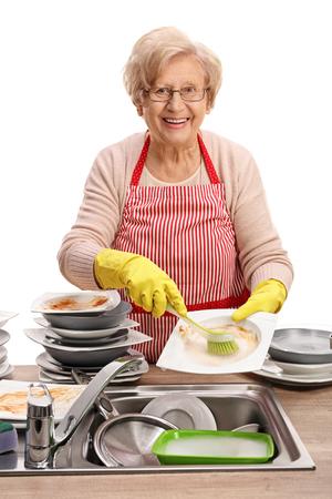 lavar platos: Mujer madura que la limpieza de los platos con un cepillo y mirando a la cámara aislada en el fondo blanco