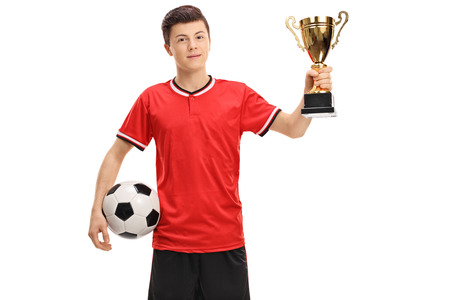 Teenage soccer player with a football and a golden trophy isolated on white background