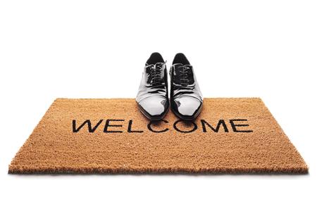 白い背景の分離が書かれた歓迎の言葉と玄関マットで靴のペア