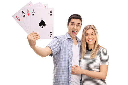 Cheerful young couple with four aces playing cards isolated on white background