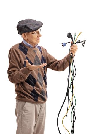 Confused Senior Blick auf elektronischen Kabeln isoliert auf weißen Hintergrund