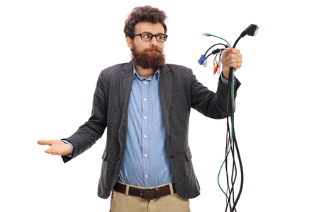 Confused guy looking at different types of electronic cables isolated on white background