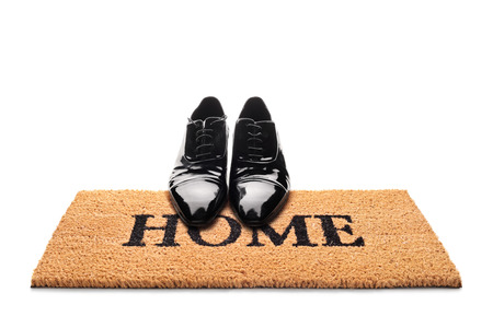 Pair of shoes on a doormat with the word home written on it isolated on white background