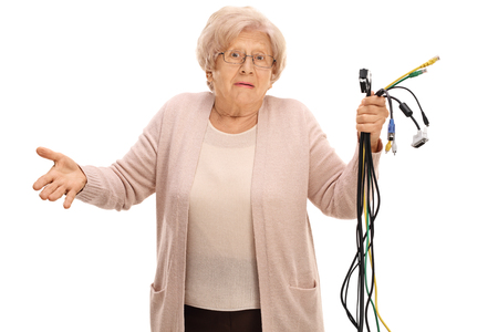 Confused elderly woman holding different types of electronic cables and looking at the camera isolated on white background