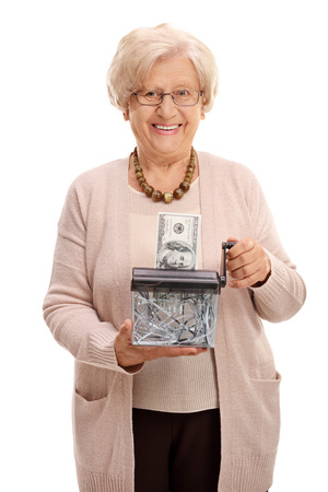 burning money: Elderly woman destroying a dollar banknote in a paper shredder isolated on white background